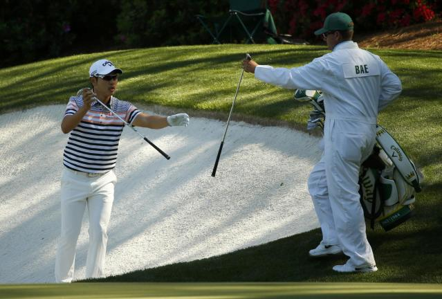 Bae Sang-moon of South Korea exchanges clubs with his caddie before hitting from a sand trap on the 13th hole during the first round of the Masters golf tournament at the Augusta National Golf Club in Augusta, Georgia April 10, 2014. REUTERS/Mike Blake (UNITED STATES - Tags: SPORT GOLF)