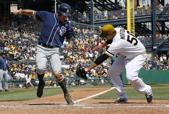 San Diego Padres' Seth Smith, left, avoids the tag by Pittsburgh Pirates starting pitcher Charlie Morton as he scores from third on a wild pitch by Morton to Padres' Yonder Alonso in the fifth inning of the baseball game on Sunday, Aug. 10, 2014, in Pittsburgh. (AP Photo/Keith Srakocic)