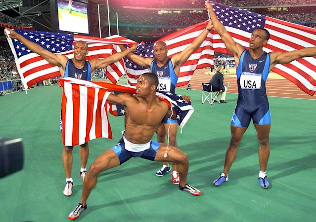 Maurice Greene, top left, Brian Lewis, top center, Jonathan Drummond, right, and Bernard Williams III, lower center, pose with U.S. flags after winning the gold medal in the men's 4 x 100 meter relay at the Summer Olympics Saturday, Sept. 30, 2000, at Olympic Stadium in Sydney. (AP Photo/Thomas Kienzle)