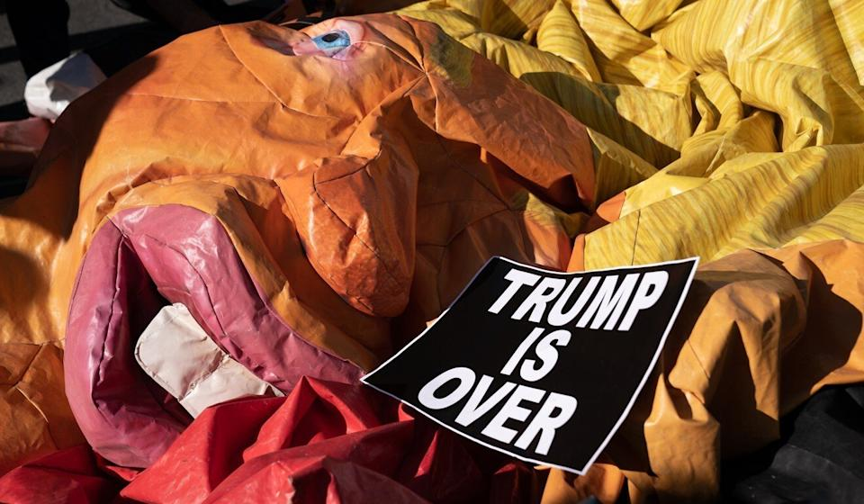 A deflated Trump float and a protest sign during celebration as Joe Biden is declared the winner of the US presidential election in Washington on Saturday. Photo: Bloomberg