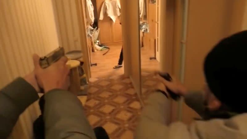 Belarusian security officers enter an apartment during a raid in Minsk