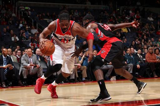WASHINGTON, DC - FEBRUARY 18: Nene #42 of the Washington Wizards drives against Patrick Patterson #54 of the Toronto Raptors during the game at the Verizon Center on February 18, 2014 in Washington, DC. (Photo by Ned Dishman/NBAE via Getty Images)