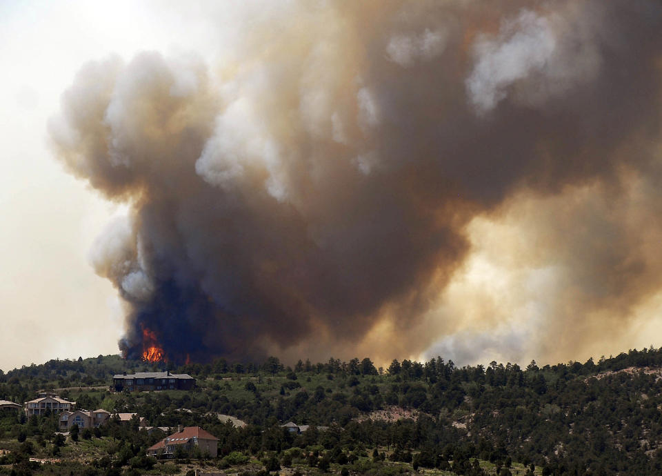 Smoke billows from a wildfire west of Colorado Springs, Colo. on Saturday, June 23, 2012. The fire has grown to an estimated 600 acres and The Gazette reports authorities are evacuating the exclusive Cedar Heights neighborhood as well as the Garden of the Gods nature center. (AP Photo/Bryan Oller)