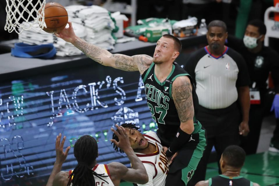 Boston Celtics' Daniel Theis (27) shoots over Cleveland Cavaliers' Darius Garland, bottom, during the first half of an NBA basketball game, Sunday, Jan. 24, 2021, in Boston. (AP Photo/Michael Dwyer)