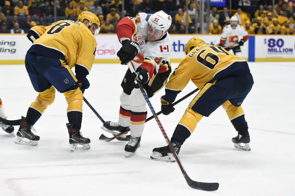 Calgary Flames center Sam Bennett (93) moves the puck between Nashville Predators' Kyle Turris (8) and Mikael Granlund (64), of Finland, during the first period of an NHL hockey game Thursday, Feb. 27, 2020, in Nashville, Tenn. (AP Photo/Mark Zaleski)