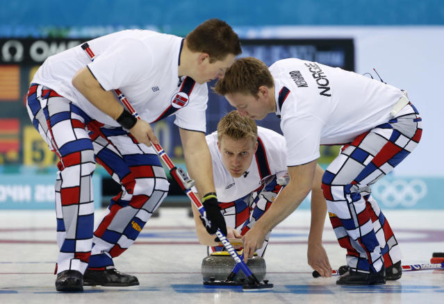 Norway's Haavard Vad Petersson, center, releases the rock to his sweepers Christoffer Svae, left, and Torger Nergaard during men's curling competition against Team USA at the 2014 Winter Olympics, Monday, Feb. 10, 2014, in Sochi, Russia. (AP Photo/Robert F. Bukaty)