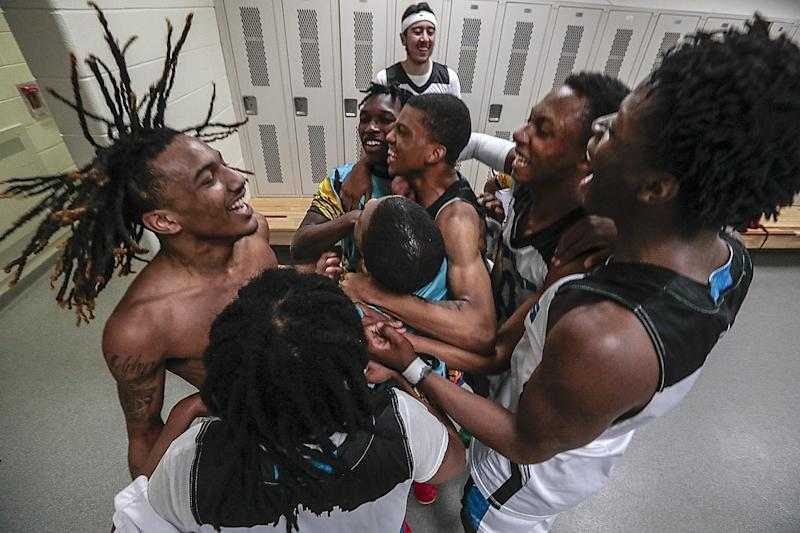 Flint players celebrate in the locker room after their win over Davison.