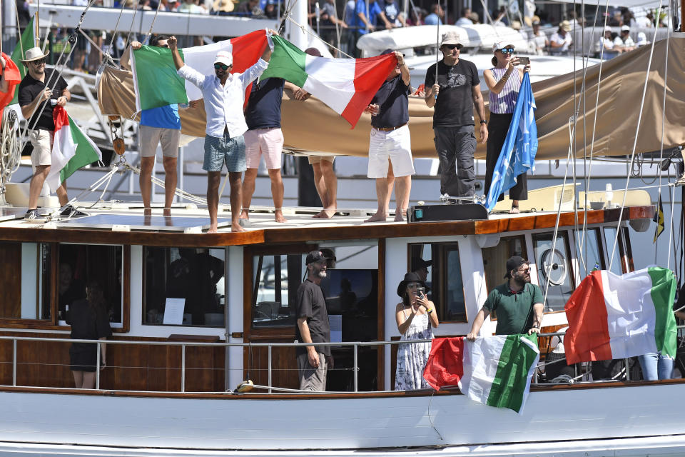 Fans of Italy's Luna Rossa cheer as the boat leaves the dock before racing Team New Zealand in race 7 of the America's Cup on Auckland's Waitemata Harbour, New Zealand, Sunday, March 14, 2021. (Alan Lee/Photosport via AP)