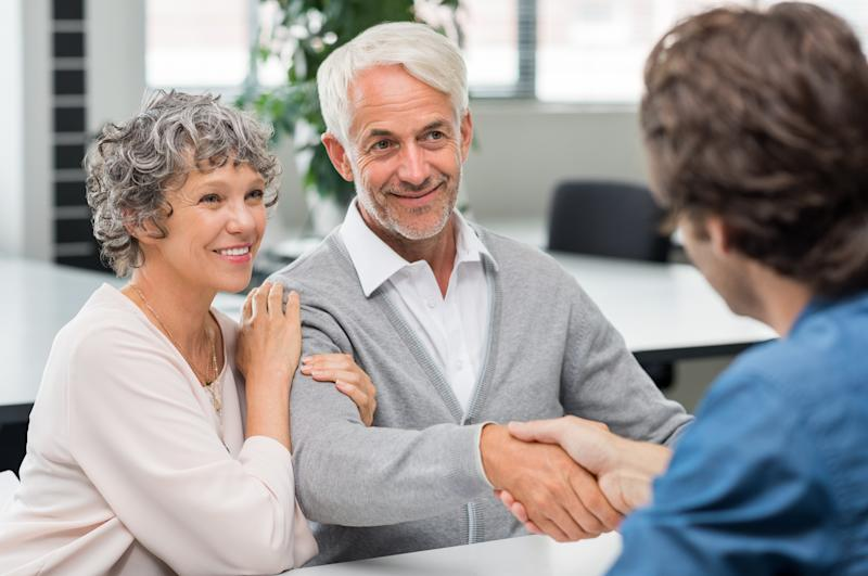 An older couple shakes hands with a younger banker at a desk.