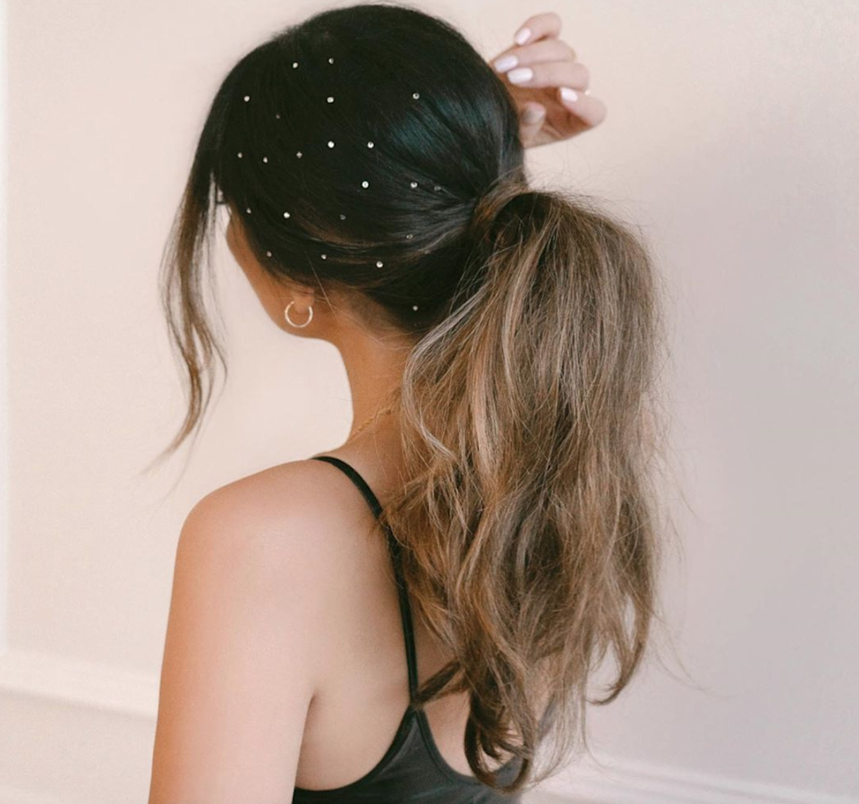 "Add a little something to a boho pony with a sprinkling of floating gemstones (<a href=""https://www.sallybeauty.com/hair/hair-accessories/stick-on-clear-crystal-hair-gems/SBS-000160.html?utm_source=google&utm_medium=cpc&adpos=1o4&scid=scplpSBS-000160&sc_intid=SBS-000160&utm_content=SBS-000160&gclid=EAIaIQobChMI_fiDwru45gIVFKSzCh2FSAGTEAQYBCABEgJNgfD_BwE&gclsrc=aw.ds"" rel=""nofollow noopener"" target=""_blank"" data-ylk=""slk:these"" class=""link rapid-noclick-resp"">these</a> stick right on your hair)."