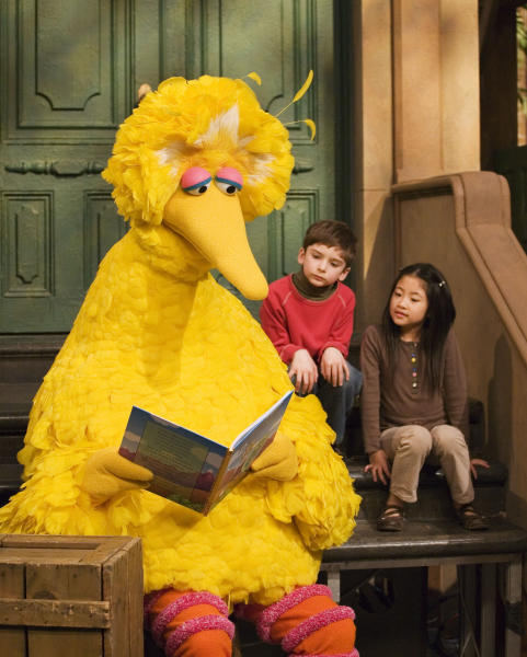 File - In this April 10, 2008, file photo, Big Bird reads to Connor Scott and Tiffany Jiao during a taping of Sesame Street in New York. The Sesame Street company is taking its beloved, critically-acclaimed brand of educational television into the highly profitable world of classroom curriculum. It's a move that experts say could open the door for other companies to sink their teeth into a sacred learning space. Sesame Workshop and McGraw-Hill Education announced their new partnership Thursday, July 19, 2018. (AP Photo/Mark Lennihan, File)