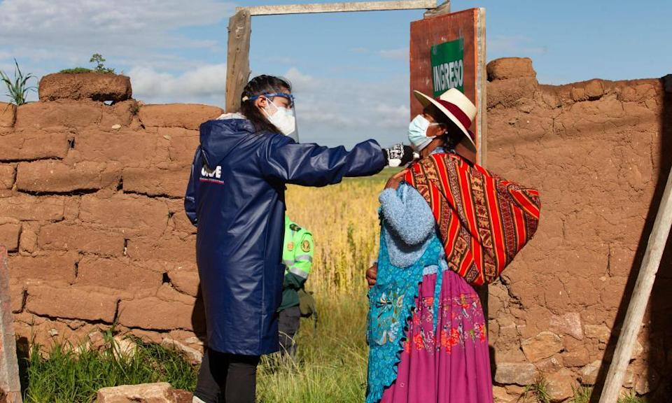 A government worker checks the temperature of a Quechua indigenous peasant arriving to vote in the village of Capachica, in Puno, Peru.