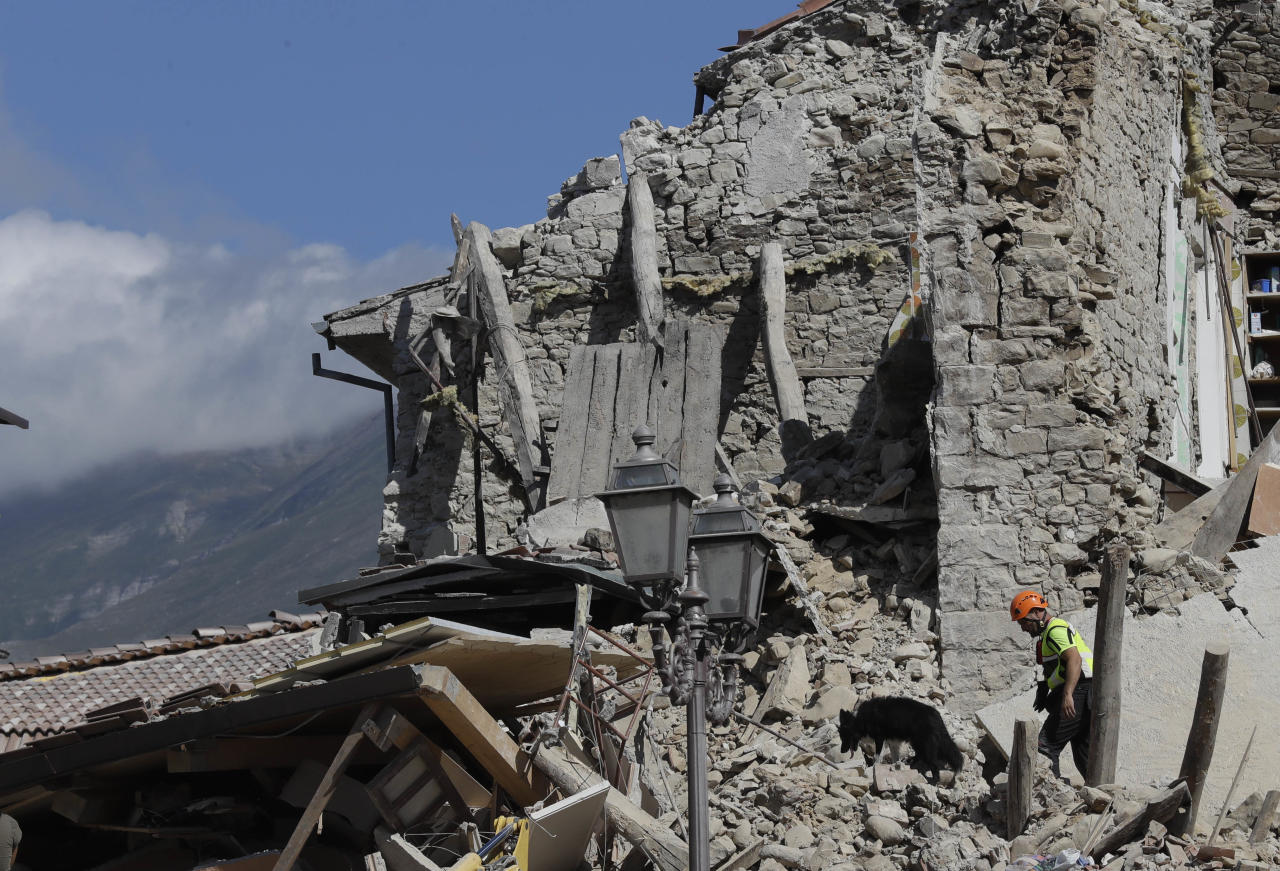 <p> A rescuer walks a sniff dog as they search through the debris of collapsed houses following an earthquake in Amatrice, central Italy, Wednesday, Aug. 24, 2016. The magnitude 6 quake struck at 3:36 a.m. (0136 GMT) and was felt across a broad swath of central Italy, including Rome where residents of the capital felt a long swaying followed by aftershocks. (AP Photo/Alessandra Tarantino) </p>