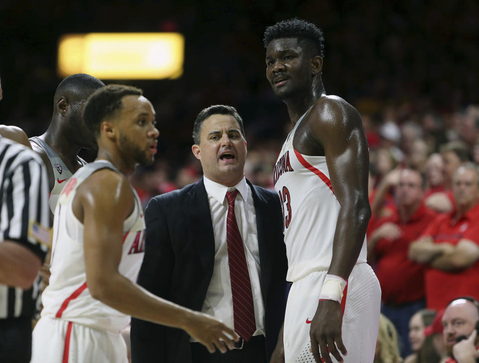 Arizona head coach Sean Miller, center, talks with forward Deandre Ayton (13) during the second half of an NCAA college basketball game against Arizona State, Saturday, Dec. 30, 2017, in Tucson, Ariz. (AP Photo/Ralph Freso)