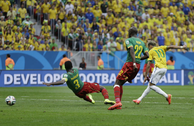 Brazil's Neymar gets a shot off between Cameroon's Nicolas N'Koulou and Cameroon's Allan Nyom to score his side's second goal during the group A World Cup soccer match between Cameroon and Brazil at the Estadio Nacional in Brasilia, Brazil, Monday, June 23, 2014. (AP Photo/Natacha Pisarenko)