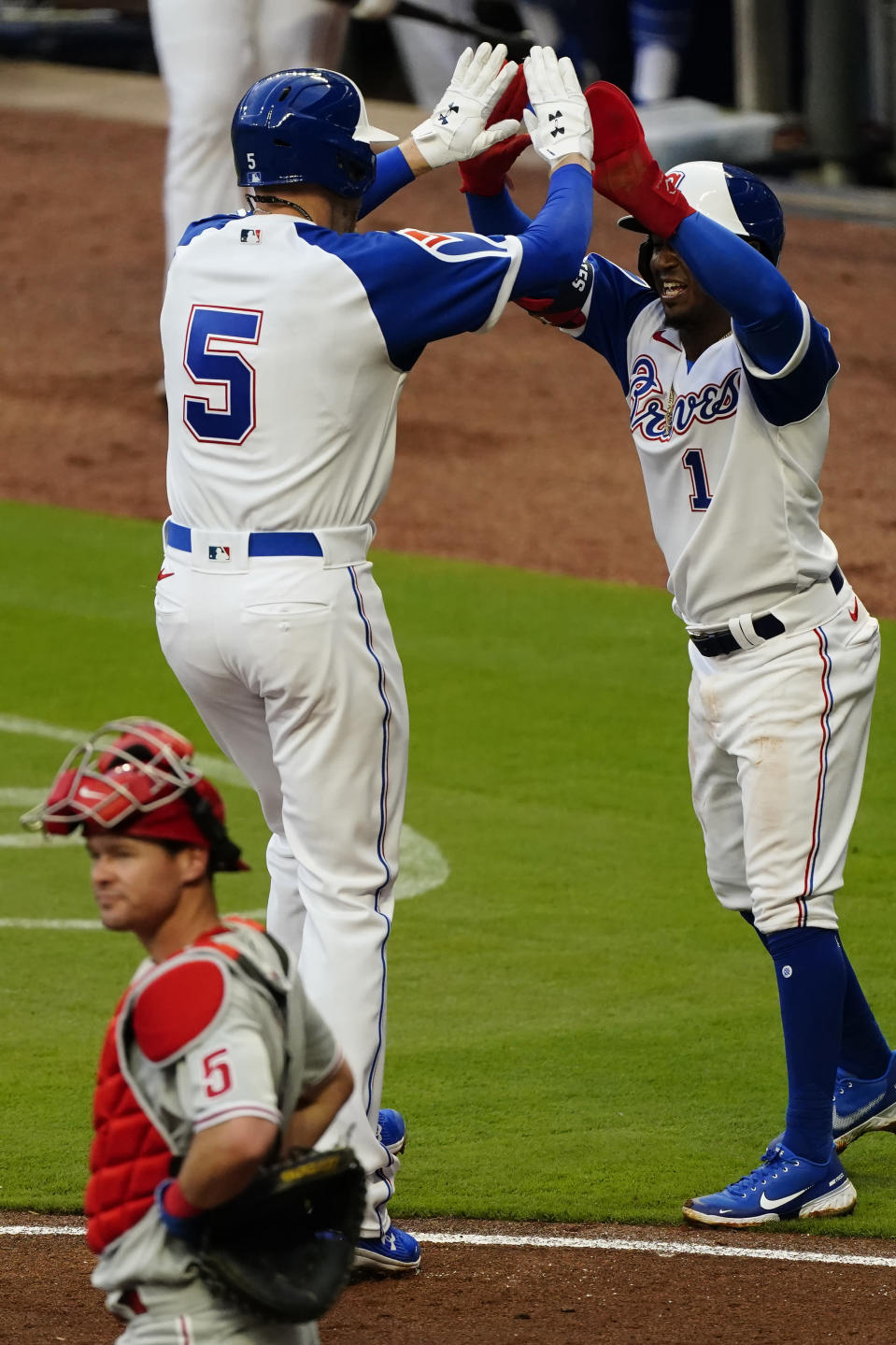 Atlanta Braves' Freddie Freeman (5) celebrates with Ozzie Albies after hitting a two-run home run in the first inning of a baseball game against the Philadelphia Phillies, Saturday, April 10, 2021, in Atlanta. Phillies catcher Andrew Knapp (5) looks on. (AP Photo/John Bazemore)
