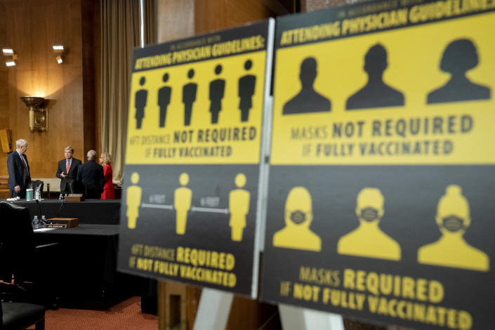 Signs requiring masks if not vaccinated against COVID-19 are displayed as National Institutes of Health Director Francis Collins, Sen. Roy Blunt, R-Mo., Dr. Anthony Fauci, director of the National Institute of Allergy and Infectious Diseases, and Diana Bianchi, director of the Eunice Kennedy Shriver National Institute of Child Health and Human Development, speak after a Senate Appropriations Subcommittee looking into the budget estimates for National Institute of Health (NIH) and the state of medical research, Wednesday, May 26, 2021, on Capitol Hill in Washington. (Stefani Reynolds/Pool via AP)