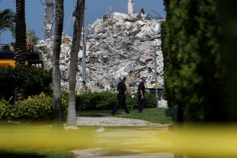 Search teams walk by the remains of the Surfside's Champlain Towers South condominium in Miami, Florida