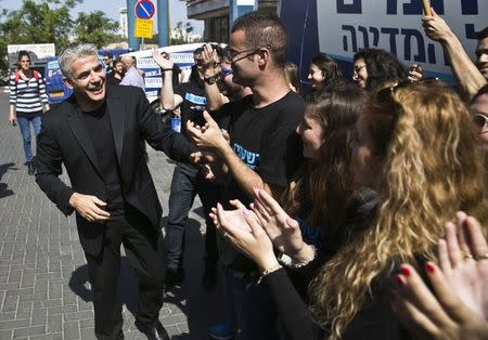 Yesh Atid leader Yair Lapid (L) shakes hands with supporters in Tel Aviv before heading on a campaign tour March 15, 2015.  REUTERS/Baz Ratner