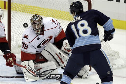 Pittsburgh Penguins' James Neal (18) has a shot blocked by Carolina Hurricanes goalie Justin Peters (35) in the first period of an NHL hockey game in Pittsburgh on Tuesday, Dec. 27, 2011. (AP Photo/Gene J. Puskar)