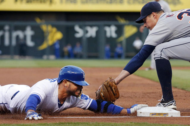 Kansas City Royals' Omar Infante, left, beats the tag by Detroit Tigers third baseman Don Kelly, right, during the first inning of a baseball game in Kansas City, Mo., Friday, May 2, 2014. Infante tripled on the play. He then scored on a sacrifice fly by teammate Eric Hosmer. (AP Photo/Orlin Wagner)
