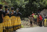 Children watch bridesmaids as they check their phones at a traditional marriage ceremony in the capital Harare, Zimbabwe Saturday, March 6, 2021. Many people across Africa are rethinking big, bountiful weddings amid the economic ravages of COVID-19 and the coronavirus pandemic is forcing change in communities where family can mean a whole clan and weddings are seen as key in cementing relations between communities. (AP Photo/Tsvangirayi Mukwazhi)