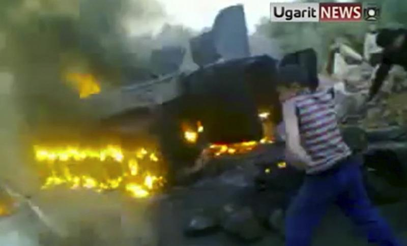 In this image from amateur video made available by the Ugarit  News group on Tuesday Nov. 15, 2011 shows a boy throwing an object at a vehicle as a Syrian tank  burns in Daraa, Syria on Monday Nov. 14, 2011.  (AP Photo/Ugarit vai APTN)  TV OUT THE ASSOCIATED PRESS CANNOT INDEPENDENTLY VERIFY THE CONTENT, DATE, LOCATION OR AUTHENTICITY OF THIS MATERIAL. TV OUT