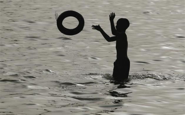 A boy plays with a rubber tube inside a pond on a hot summer day at in New Delhi May 31, 2012.