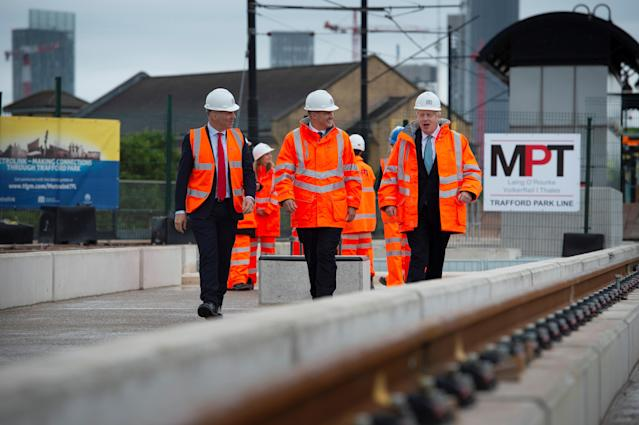 Prime minister Boris Johnson walks with CEO of Transport for the North, Barry White and Northern Powerhouse minister, Jake Berry as he visits the site of an under-construction tramline in Stretford, near Manchester, Britain. Photo: Geoff Pugh/Reuters