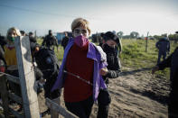 Women are detained by police carrying out evictions at a squatters camp in Guernica, Buenos Aires province, Argentina, Thursday, Oct. 29, 2020. A court ordered the eviction of families who are squatting here since July, but the families say they have nowhere to go amid the COVID-19 pandemic. (AP Photo/Natacha Pisarenko)