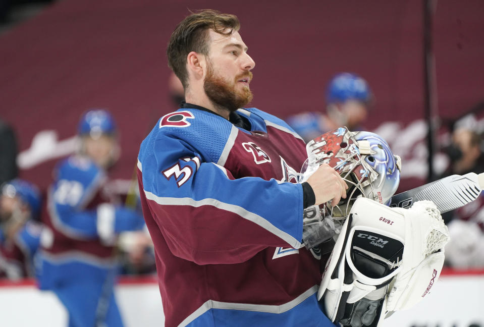 Colorado Avalanche goaltender Philipp Grubauer adjusts the straps on his mask as he heads back to the net during a timeout in the first period of an NHL hockey game against the Arizona Coyotes, Monday, April 12, 2021, in Denver. (AP Photo/David Zalubowski)