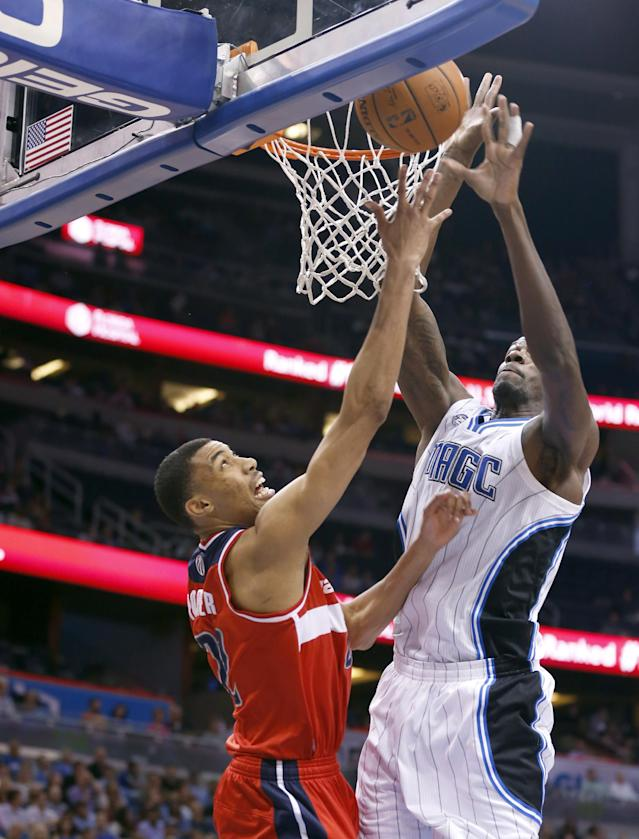 Washington Wizards forward Otto Porter Jr., left, shoots against Orlando Magic center Dewayne Dedmon, right, during the first half of an NBA basketball game in Orlando, Fla., Friday, April 11, 2014. (AP Photo/Reinhold Matay)