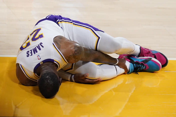 Los Angeles Lakers forward LeBron James holds his ankle after going down with an injury during the first half of an NBA basketball game against the Atlanta Hawks Saturday, March 20, 2021, in Los Angeles. (AP Photo/Marcio Jose Sanchez)