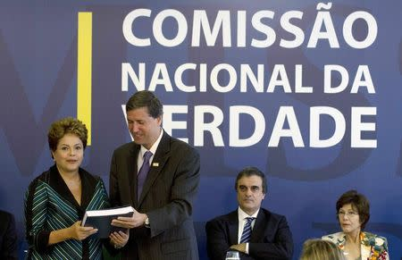 """Brazilian President Dilma Rousseff (L) receives the report from Pedro Dallari (2nd L), a member of the """"truth commission"""", in Brasilia December 10, 2014.   REUTERS/Joedson Alves"""