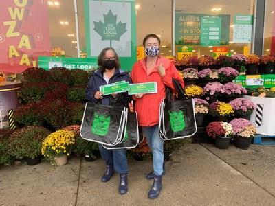Two women outside Food Basics grocery store holding information postcards (CNW Group/Unifor)