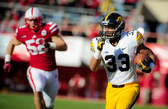 LINCOLN, NE - NOVEMBER 29: Running back Jordan Canzeri #33 of the Iowa Hawkeyes outruns linebacker Josh Banderas #52 of the Nebraska Cornhuskers during their game at Memorial stadium on November 29, 2013 in Lincoln, Nebraska. (Photo by Eric Francis/Getty Images)