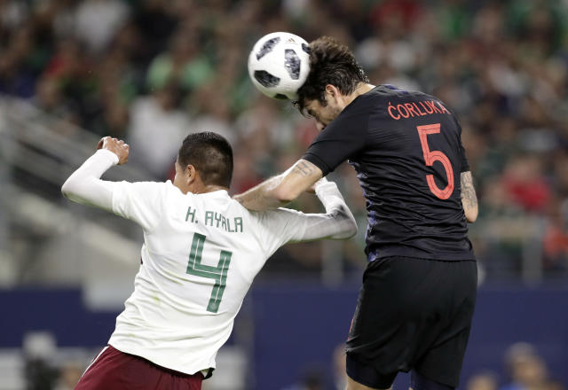 CORRECTS DATE OF PHOTO - Mexico defender Hugo Ayala (4) defends as Croatia defender Vedran Corluka (5) heads to ball at the net off a corner kick in the first half of a friendly soccer match in Arlington, Texas, Tuesday, March 27, 2018. The shot by Corluka did not score. (AP Photo/Tony Gutierrez)