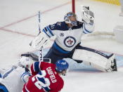 Winnipeg Jets goaltender Connor Hellebuyck (37) makes a glove save on Montreal Canadiens' Cole Caufield during the second period of an NHL Stanley Cup playoff hockey game in Montreal, Sunday, June 6, 2021. (Ryan Remiorz/The Canadian Press via AP)