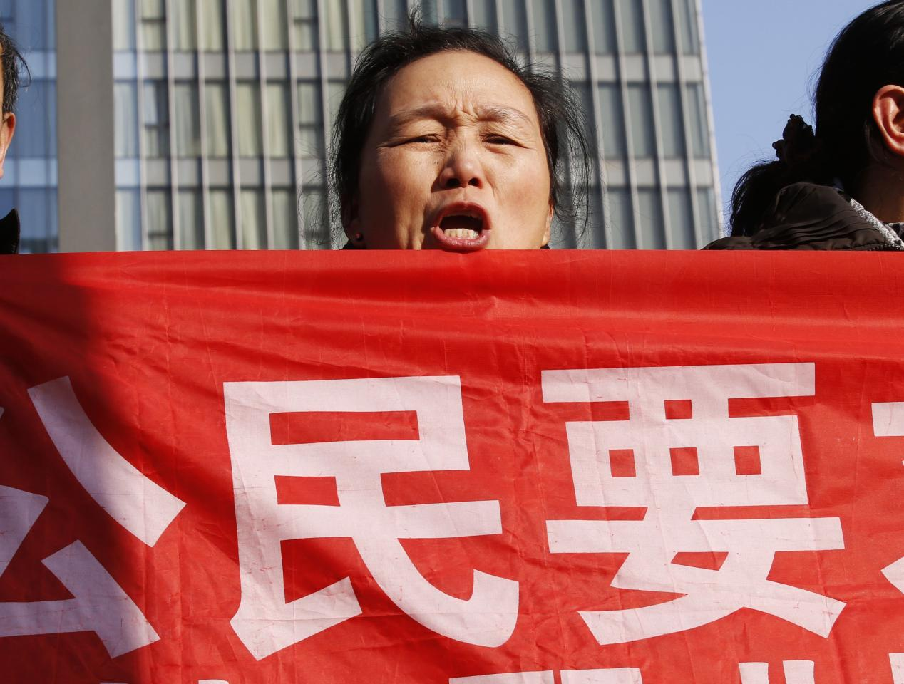 """Supporters of Xu Zhiyong, one of China's most prominent rights advocates, shout slogans near a court where Xu's trial is being held, in Beijing January 22, 2014. Xu, 40, stands trial on Wednesday on a charge of """"gathering a crowd to disturb public order"""" punishable by up to five years in prison. His case will almost certainly spark fresh criticism from Western governments over Beijing's crackdown on dissent. The slogan on the placard is a part of slogan that reads: """"Citizens request officials to publicly disclose assets."""" REUTERS/Kim Kyung-Hoon (CHINA - Tags: POLITICS CIVIL UNREST)"""