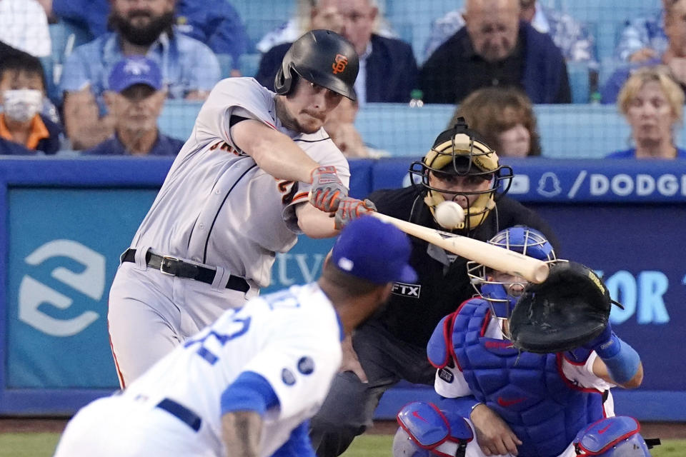 San Francisco Giants' Alex Dickerson, left, hits a two-run home run as Los Angeles Dodgers pitcher Darien Nunez, second from left, and catcher Austin Barnes, right, watch along with home plate umpire Dan Iassogna during the second inning of a baseball game Tuesday, July 20, 2021, in Los Angeles. (AP Photo/Mark J. Terrill)