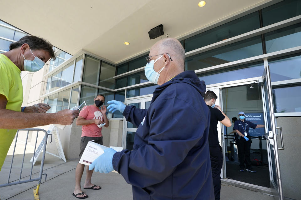 James Doyle, front right, hands out face masks as people arrive at a COVID-19 mass vaccination clinic, Wednesday, May 19, 2021, at Gillette Stadium, in Foxborough, Mass. A month after every adult in the U.S. became eligible for the vaccine, a distinct geographic pattern has emerged: The highest vaccination rates are concentrated in the Northeast, while the lowest ones are mostly in the South. (AP Photo/Steven Senne)