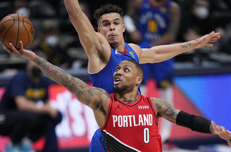 Portland Trail Blazers guard Damian Lillard (0) shoots next to Denver Nuggets forward Michael Porter Jr. (1) during the second half of Game 1 of a first-round NBA basketball playoff series Saturday, May 22, 2021, in Denver. (AP Photo/Jack Dempsey)