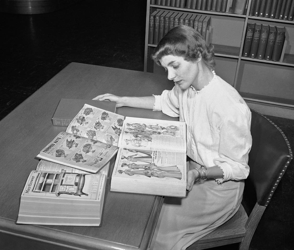 FILE - In an undated file photo, Ruth Parrington, librarian in the art department of the Chicago Public Library, studies early Sears Roebuck catalogs in the library's collection in Chicago. The catalog Parrington is holding features women's fashion from 1902. Sears has filed for Chapter 11 bankruptcy protection Monday, Oct. 15, 2018, buckling under its massive debt load and staggering losses. (AP Photo/File)