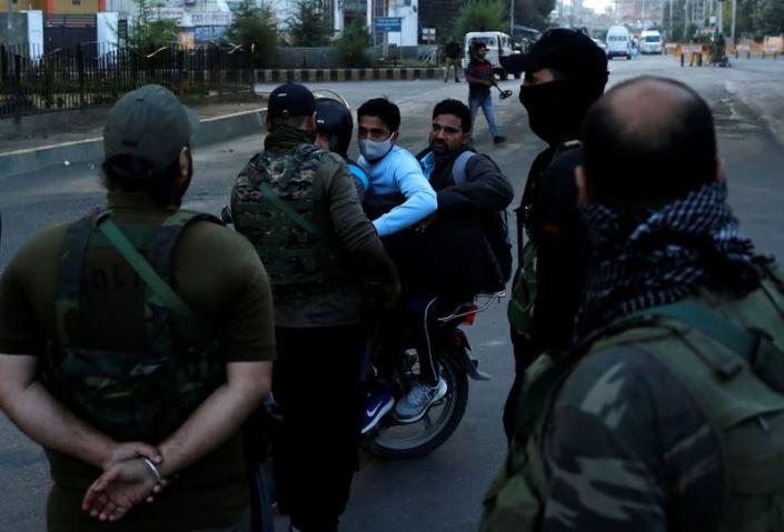 Indian security force personnel stop men riding a motorcycle at a barricade near the residence of Syed Ali Shah Geelani after his death in Srinagar