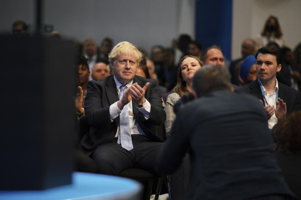 Britain's Prime Minister Boris Johnson applauds as Chancellor of the Exchequer Rishi Sunak speaks during the Conservative Party Conference in Manchester, England, Monday, Oct. 4, 2021. (Peter Byrne/PA via AP)