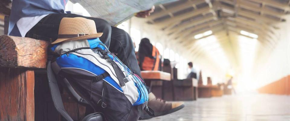 Backpack and hat at the train station with a traveler. Travel concept.
