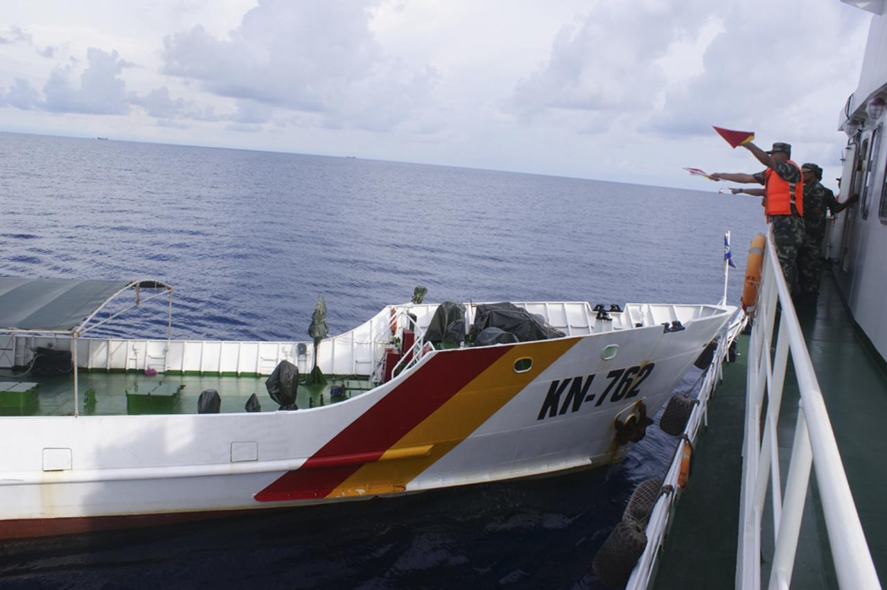 A Chinese maritime policeman (R) uses flags to signal to Vietnamese ship KN-762 (L), which according to Chinese authorities collided with Chinese coast guard ship 46001 in South China Sea, in this handout dated May 2, 2014 provided by Chinese Ministry of Foreign Affairs on June 13, 2014. A Chinese official said on Friday that China will never send military forces to the scene of an increasingly ugly spat with Vietnam over an oil rig in the South China Sea, and accused Hanoi of trying to force an international lawsuit. REUTERS/Ministry of Foreign Affairs/Handout via Reuters (CHINA - Tags: POLITICS MILITARY) CHINA OUT. NO COMMERCIAL OR EDITORIAL SALES IN CHINA. ATTENTION EDITORS: THIS PICTURE WAS PROVIDED BY A THIRD PARTY. REUTERS IS UNABLE TO INDEPENDENTLY VERIFY THE AUTHENTICITY, CONTENT, LOCATION OR DATE OF THIS IMAGE. NO SALES. NO ARCHIVES. FOR EDITORIAL USE ONLY. NOT FOR SALE FOR MARKETING OR ADVERTISING CAMPAIGNS. THIS PICTURE IS DISTRIBUTED EXACTLY AS RECEIVED BY REUTERS, AS A SERVICE TO CLIENTS