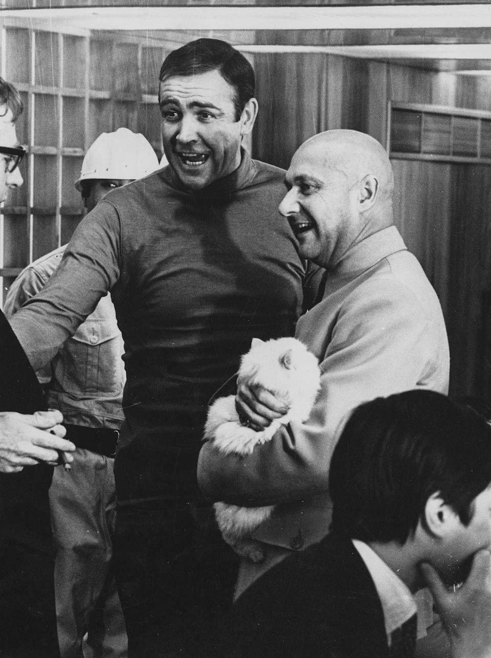 <p>Sean Connery and Donald Pleasance (in costume as Blofeld holding a cat) chatting in between scenes on the set of You Only Live Twice.</p>