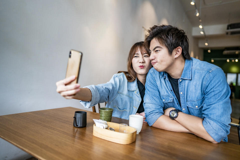 Young Asian couple taking selfie while drinking coffee in cafe coffee shop