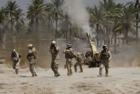 Iraqi soldiers fire artillery during clashes with Sunni militant group Islamic State of Iraq and the Levant (ISIL) in the town of Jurf al-Sakhar